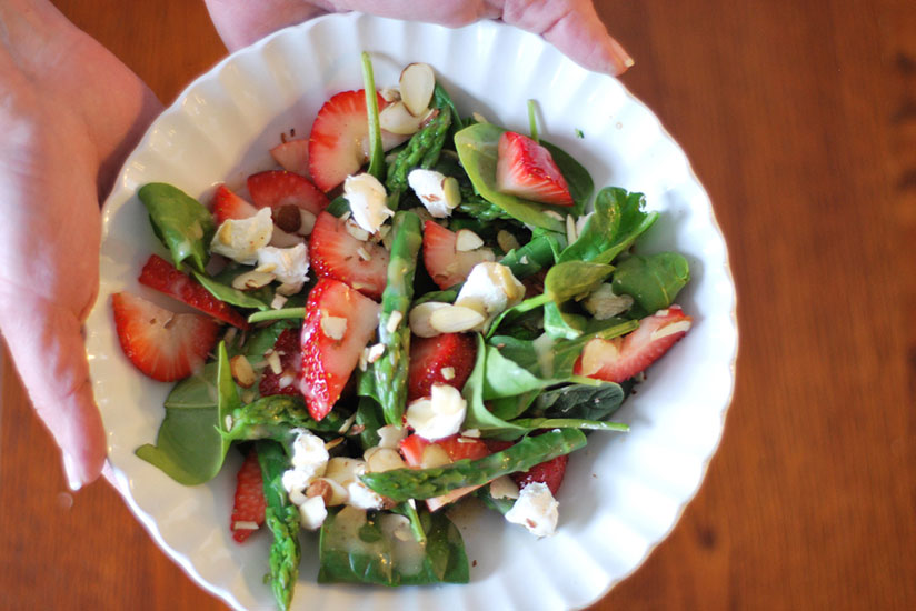 Hands holding plate of spinach, asparagus, and strawberry salad with goat cheese
