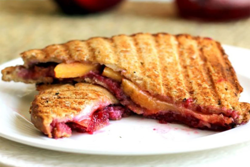 Diagonally cut strawberry and peach panini on white plate on table