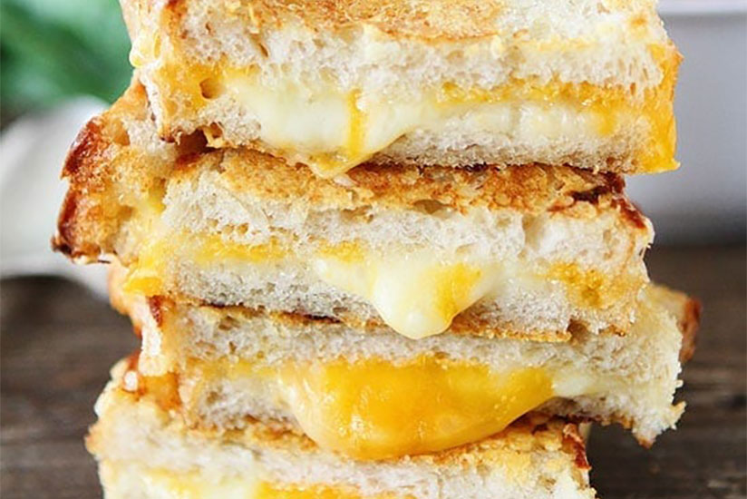 Stack of three cheeses grilled cheese sandwiches on top of wood tray