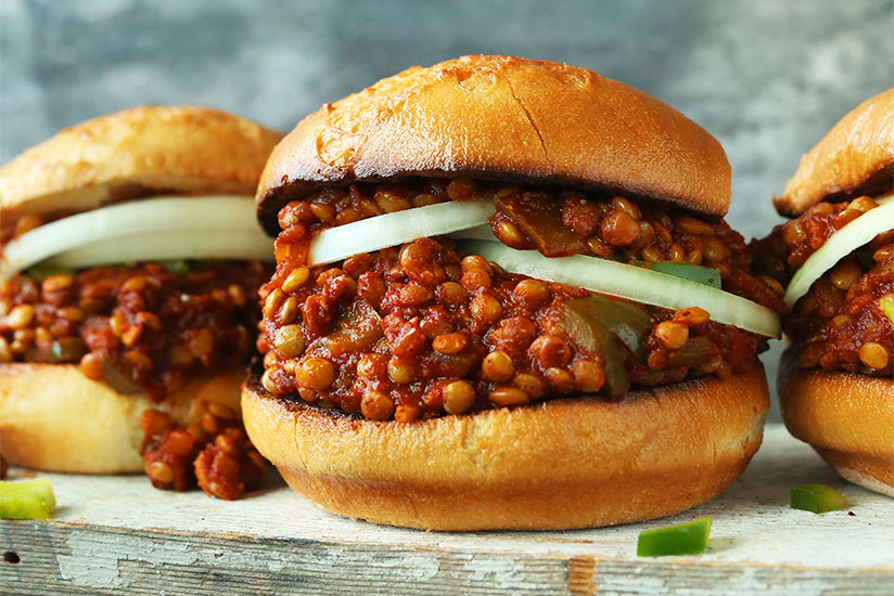 Three lentil sloppy joes with white onion on wood counter on gray background