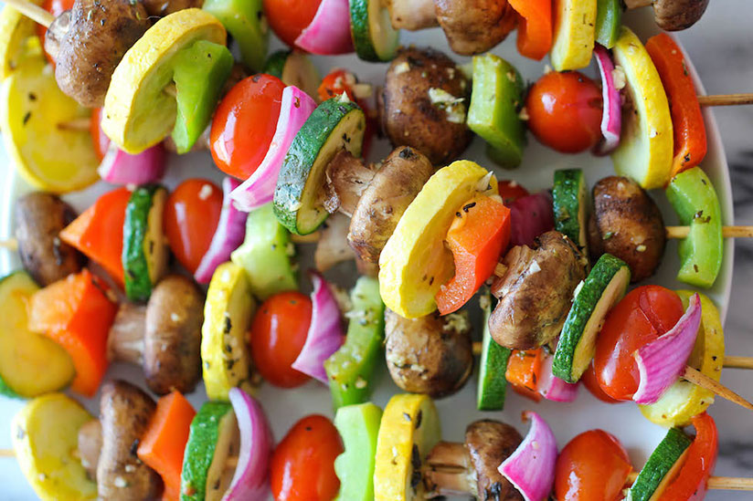 Sliced grilled tomatoes, squash, onions, and zucchinis in skewers on plate