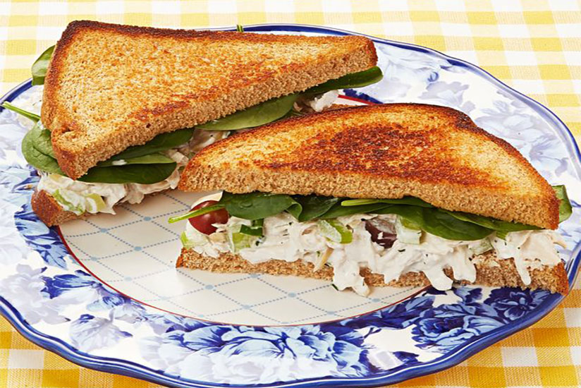 Diagonally cut chicken salad sandwich with toasted bread on blue and white plate