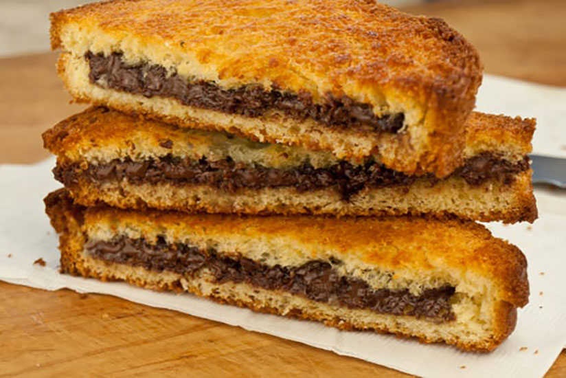 Stack of chocolate pressed sandwiches on white paper on wood counter