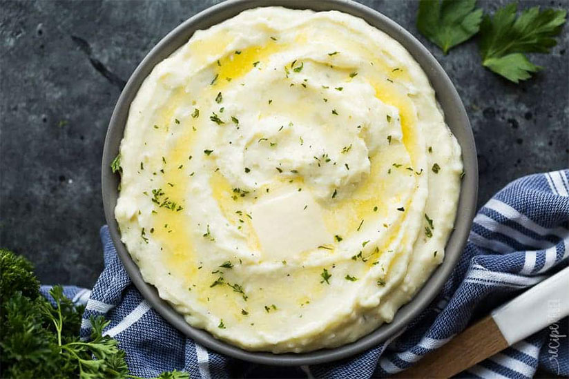 Cream cheese mashed potatoes sprinkled with chopped herbs in gray bowl