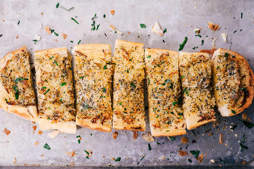 Sliced oven baked garlic bread sprinkled with herbs on counter