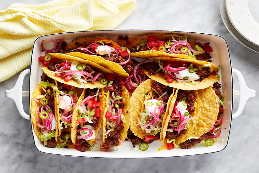 Ground beef tacos topped with sliced jalapenos in white rectangular dish