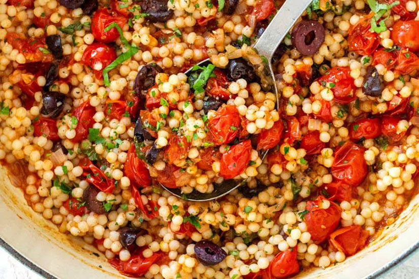 Israeli couscous with tomatoes and olives in blue and white dish on counter