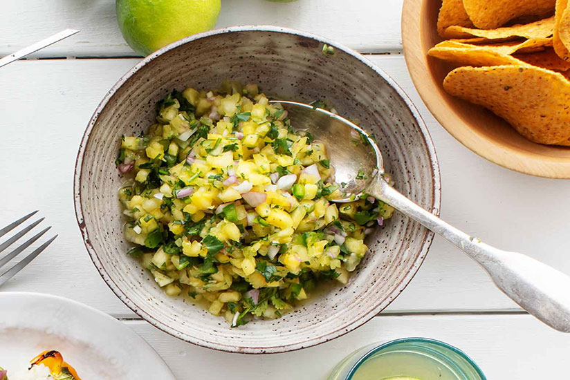 Pineapple salsa with chopped red onions in bowl with spoon on counter