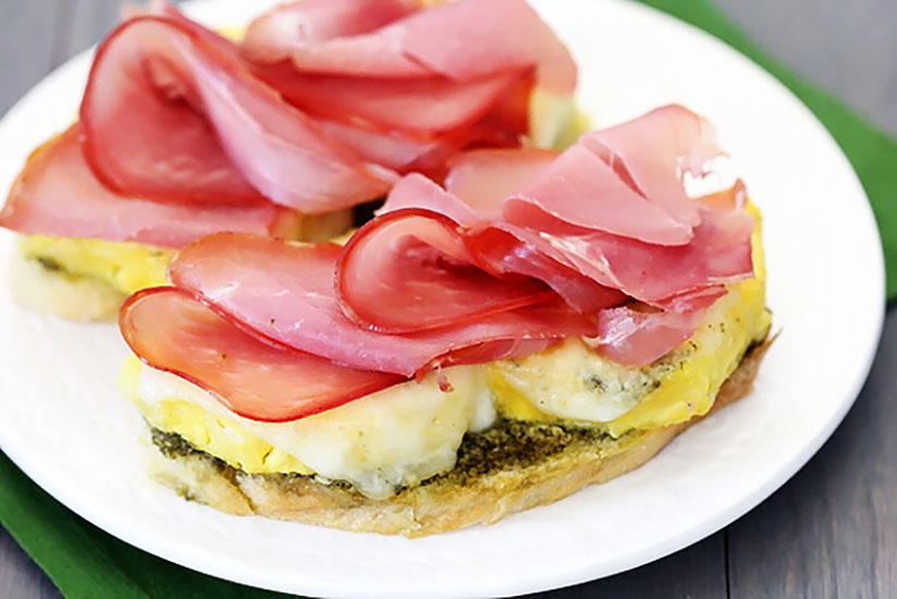 Two open face prosciutto pineapple paninis on plate on wood counter