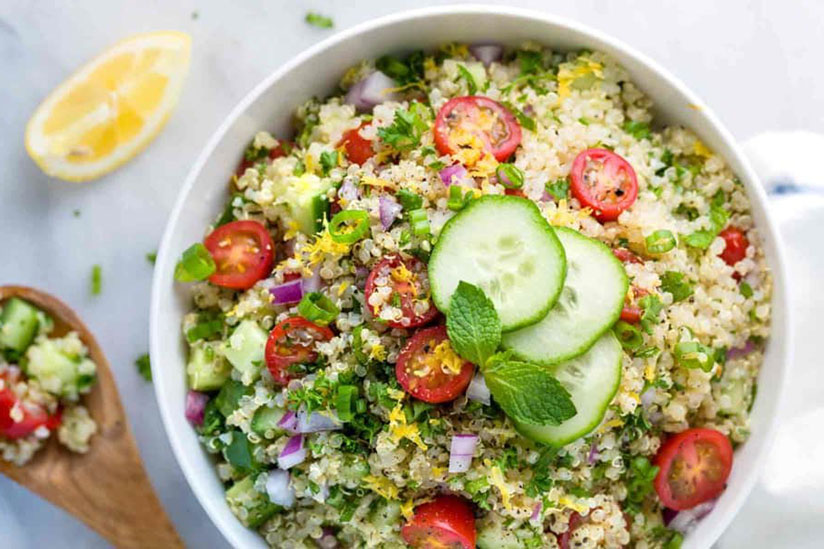 Quinoa tabbouleh in bowl topped with three slices of cucumber on counter