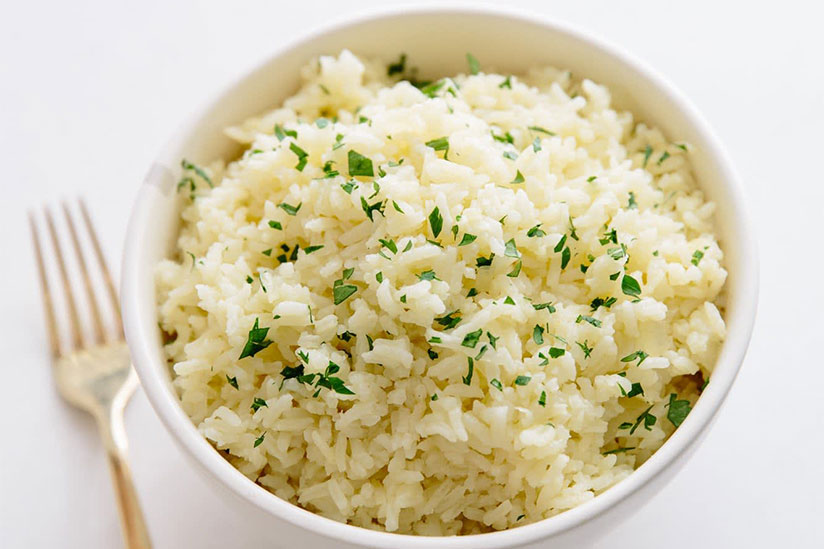 Rice pilaf sprinkled with chopped herbs in white bowl beside fork on counter