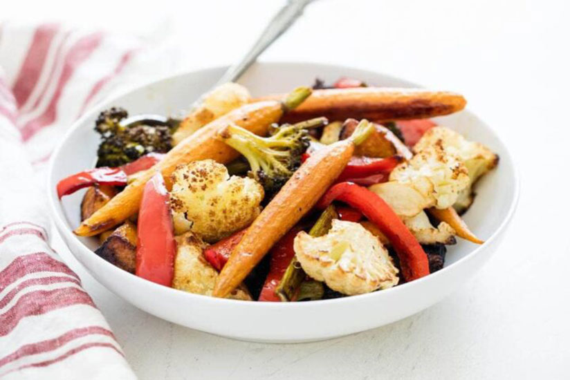Roasted winter vegetables on white plate beside red dish towel on counter