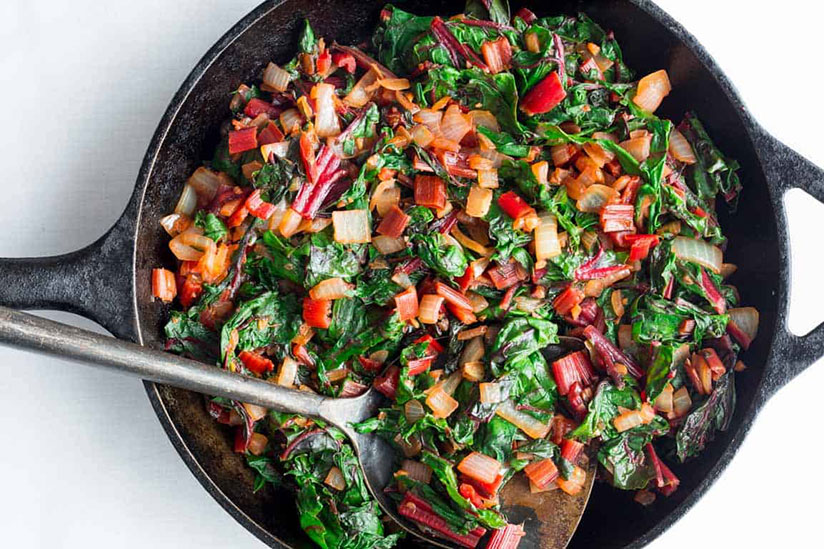Sautéed swiss chard in iron skillet with metal spatula on white counter