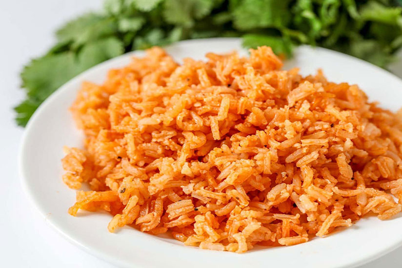 Mexican rice on white plate beside bundle of cilantro on white counter