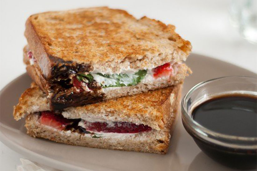 Strawberry basil and goat cheese panini with side of balsamic sauce on plate