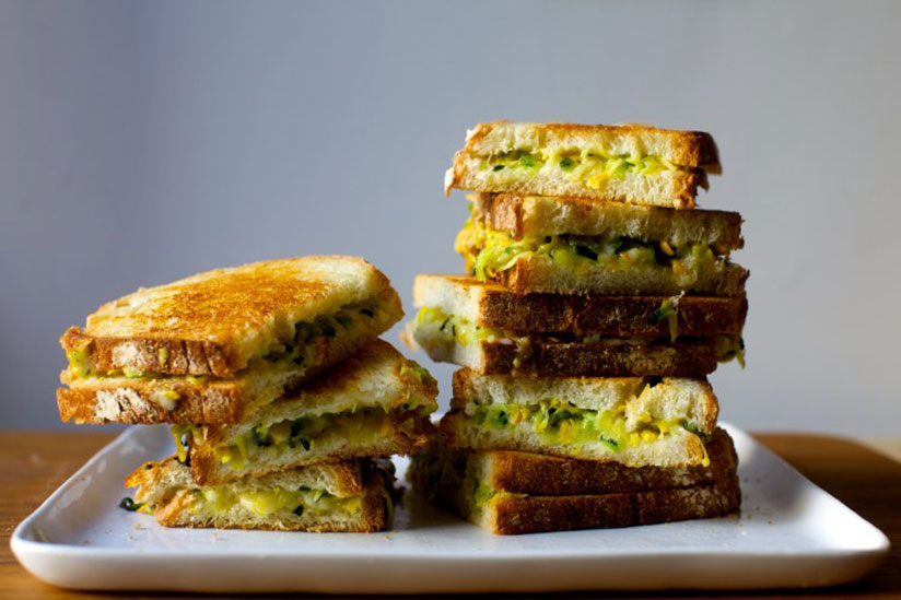 Stacks of zucchini grilled cheese sandwiches on white tray on wood counter