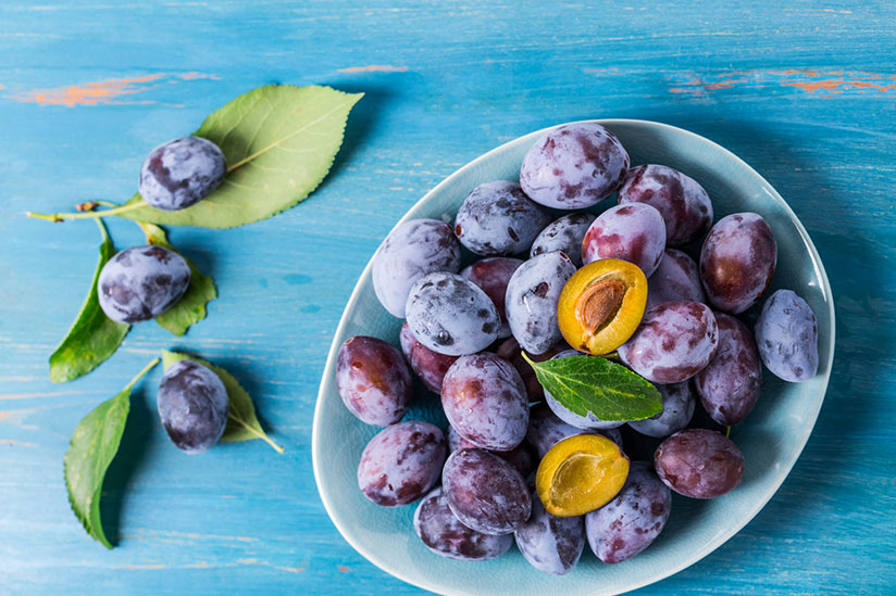 Pile of carlsbad plums on white plate with one opened on top on blue wood counter