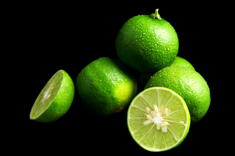Desert Limes with two cut in half isolated on black background