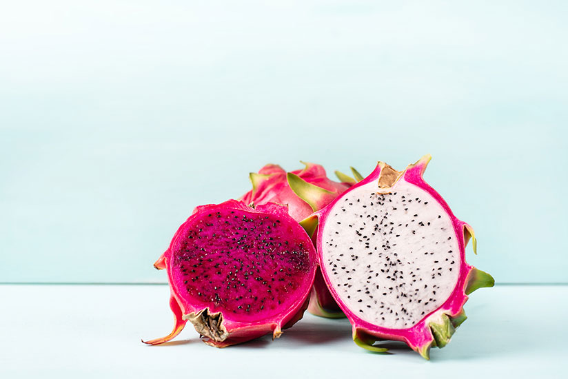 Halved red and white dragon fruits on white table on light blue background