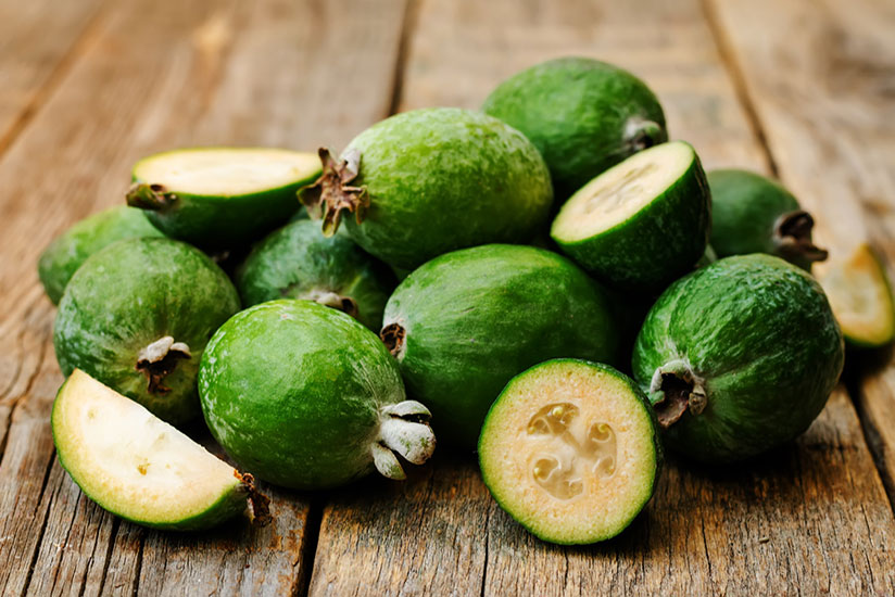Pile of Feijoa fruits on wooden surface with other pieces sliced in half