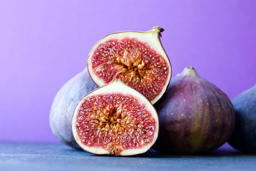 Pile of purple figs with one cut in half on purple surface and background