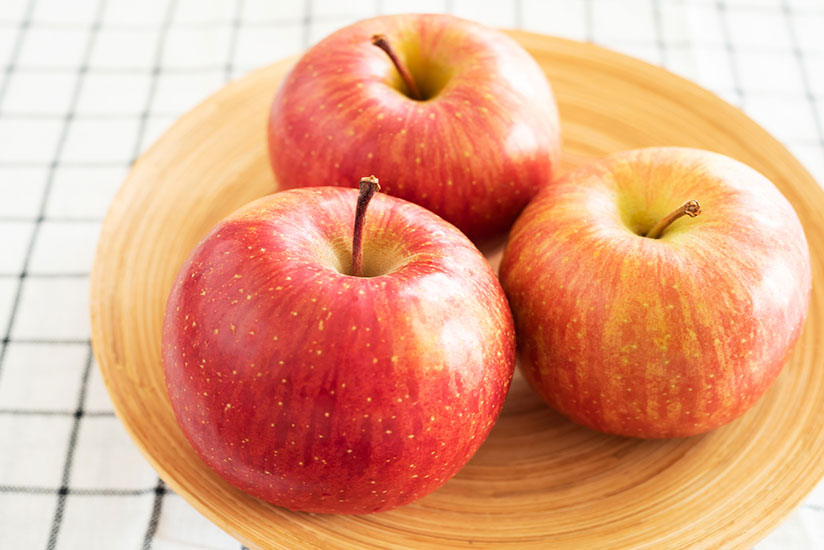 Three fresh fuji apples on wooden plate on top of black and white checkered table