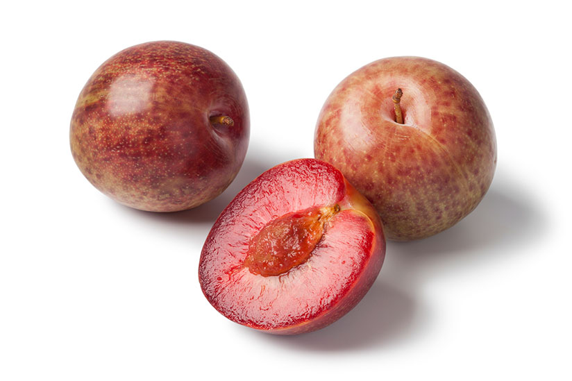 Three pluot fruits with one sliced in half isolated on white background