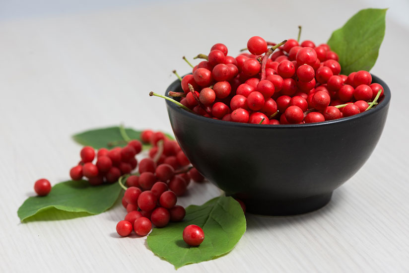 Five flavor berries in black bowl with leaves on white wood counter
