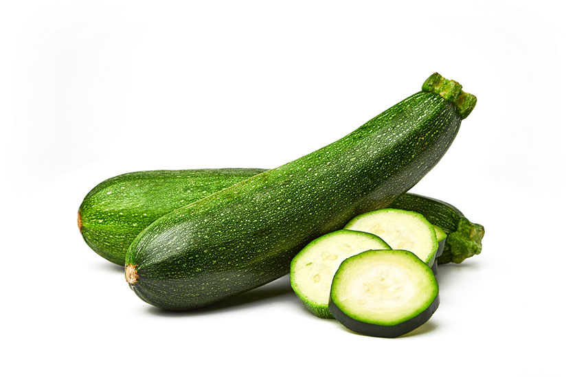 Whole zucchinis with some sliced isolated on white background